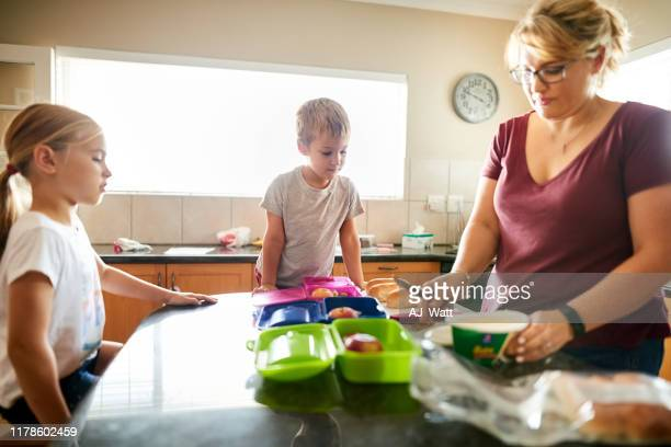 mother preparing school lunch box - preparation stock pictures, royalty-free photos & images