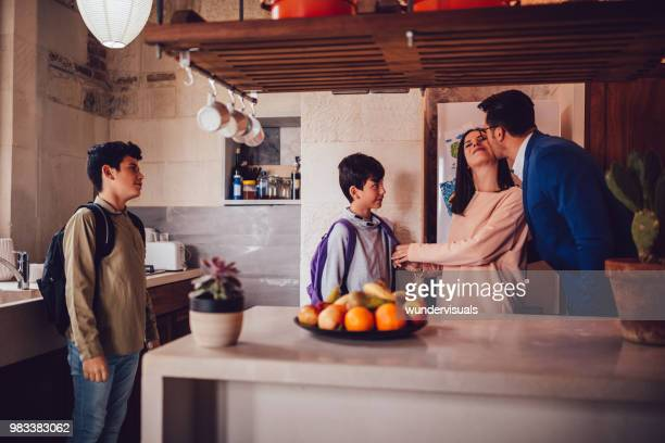préparation des fils pour l'école mère et le baiser d'adieu mari homme d'affaires - homme bisous femme photos et images de collection