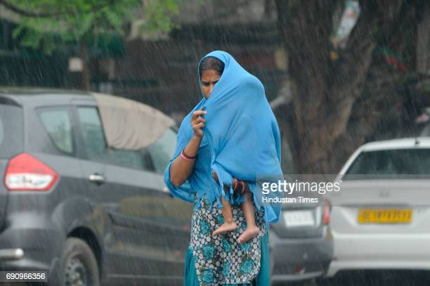 A mother protecting her child during heavy rains on May 31 2017 in New Delhi India Rains lashed parts of Delhi and NCR at midday lowering the...