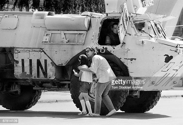 A mother protects her daughter behind the UN armoured personnel carrier during shooting in Sarajevo in 1995