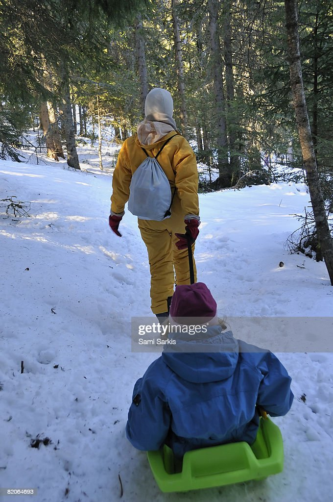 Mother pulling daughter  (7-8)  in sled in forest, French Alps, France : Stock Photo