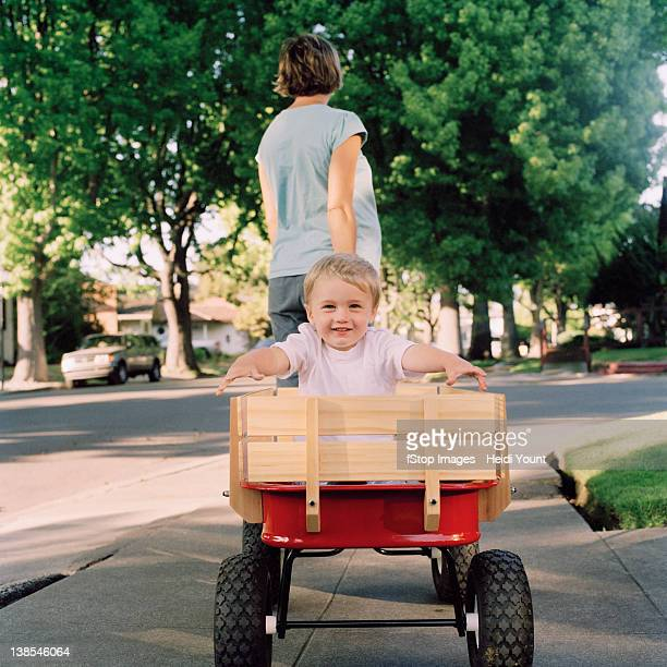 A mother pulling her young son in a wagon, focus on boy