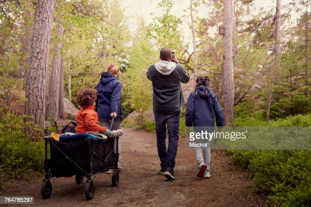 Mother pulling son sitting on cart while walking with man and daughter in forest