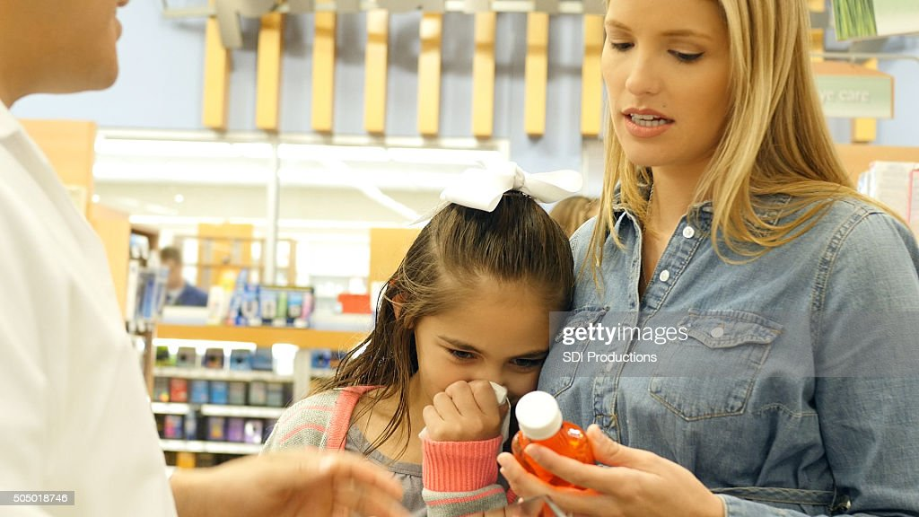 Mother purchasing cold medicine for sick elementary age daughter : Stock Photo