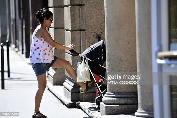 A mother pushes a baby carriage on July 11 2016 in Budapest / AFP / ATTILA KISBENEDEK