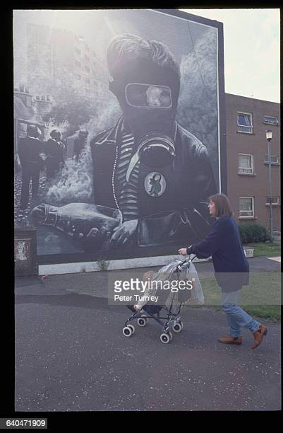 A mother pushes her child by an Irish Nationalist mural in the Catholic neighborhood of Bogside