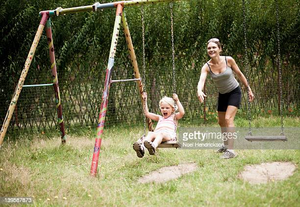 A mother pushes her daughter on a swing