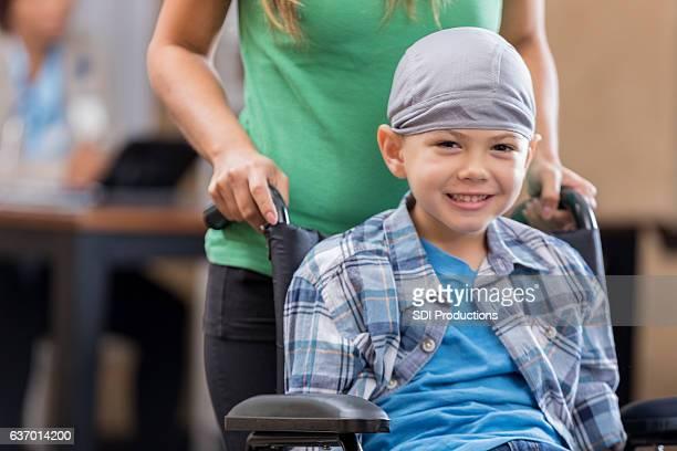 mother pushes sick little boy in wheelchair - sorriso aberto imagens e fotografias de stock