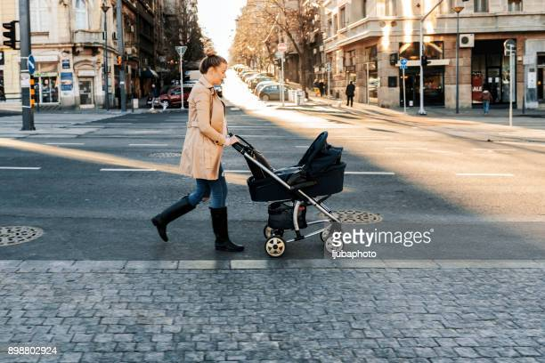 mother pushing a stroller in the street - pushchair stock pictures, royalty-free photos & images