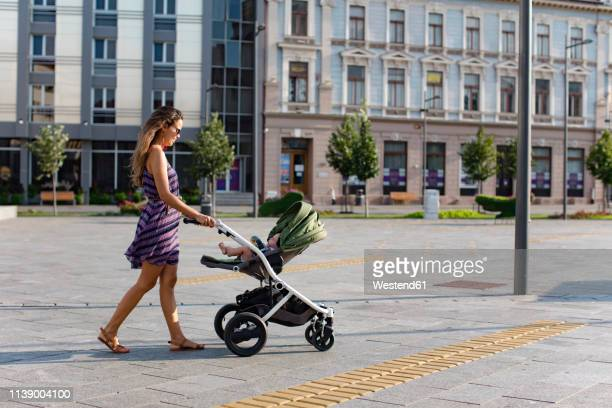 mother pushing baby in a stroller in the city - pushchair stock pictures, royalty-free photos & images
