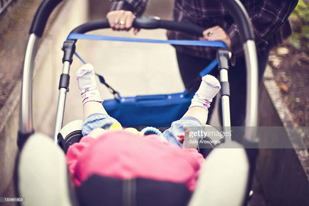 Mother pushing baby in pram : Stock Photo