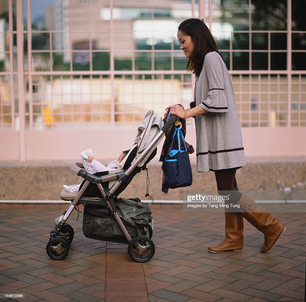 Mother pushing baby in stroller : Stock Photo