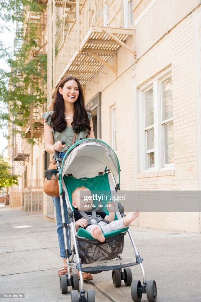 Mother pushing baby son in stroller in city : Stock Photo
