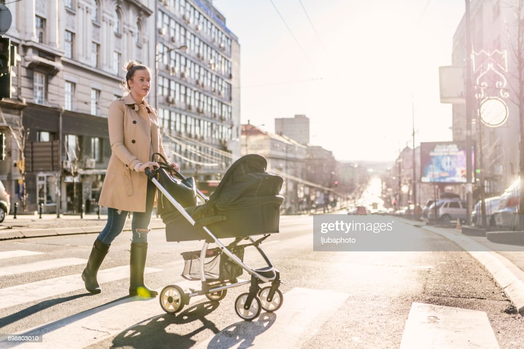 Mother pushing baby stroller on lined pedestrian crossing : Stock Photo