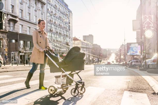mother pushing baby stroller on lined pedestrian crossing - pushchair stock pictures, royalty-free photos & images