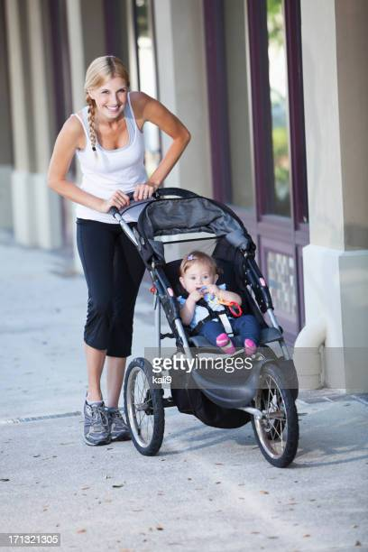 Mother pushing baby stroller on sidewalk
