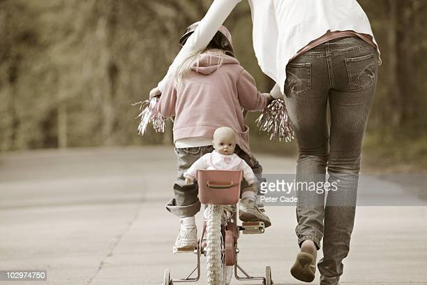 mother pushing child on bike