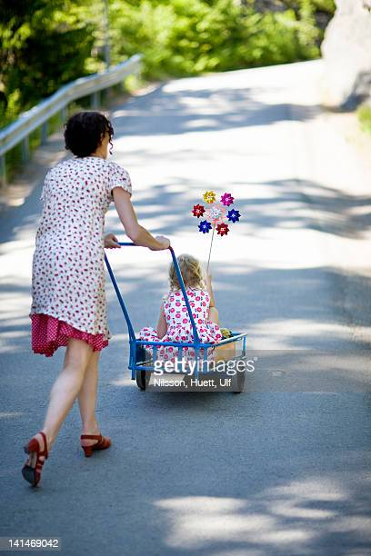 Mother pushing daughter in cart at zoo