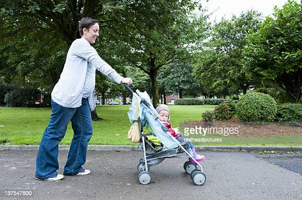 mother pushing daughter in stroller - pushchair stock pictures, royalty-free photos & images