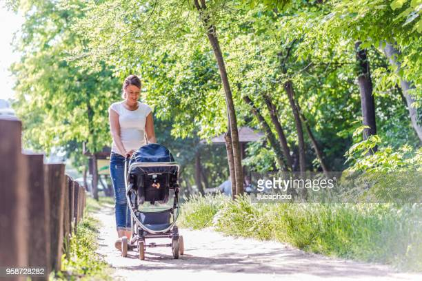 mother pushing daughter in stroller - carriage stock pictures, royalty-free photos & images