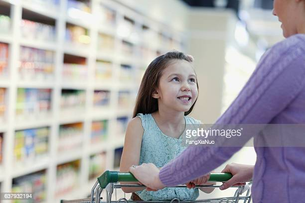 Mother pushing daughter in supermarket shopping cart
