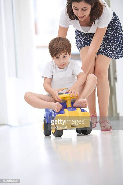 mother pushing daughter in toy car - too small stock pictures, royalty-free photos & images