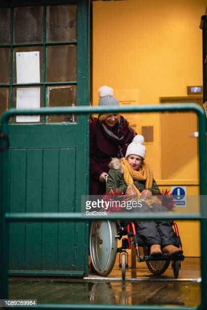 mother pushing daughter in wheelchair - epilepsy stock pictures, royalty-free photos & images