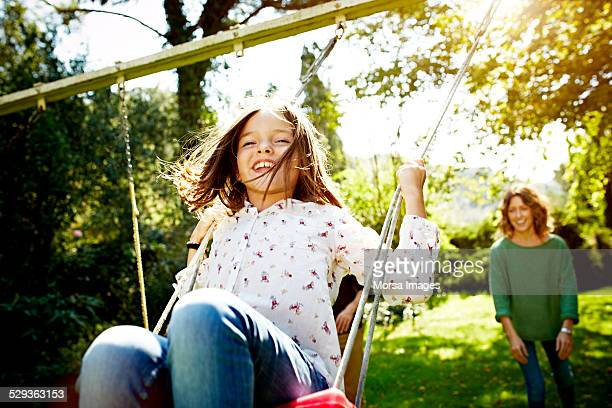 mother pushing daughter on swing in park - swinging stock pictures, royalty-free photos & images