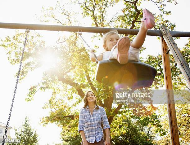 mother pushing daughter on swing in sunny park - swinging stock pictures, royalty-free photos & images