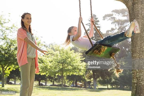 Mother pushing girl on swing