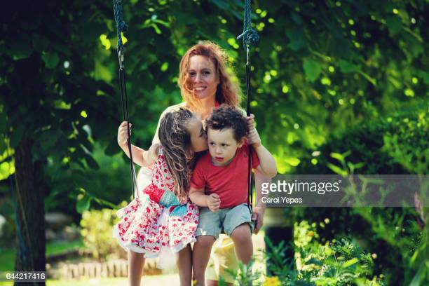 Mother pushing her child on swing