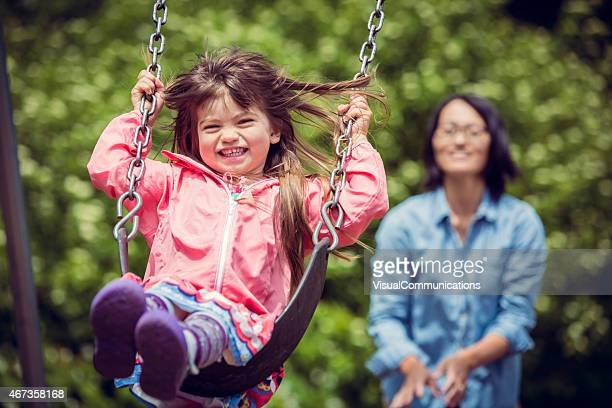 Mother pushing her daughter on swing.