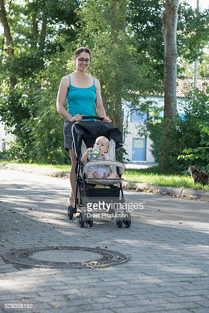 Mother pushing pram on footpath, Munich, Bavaria, Germany