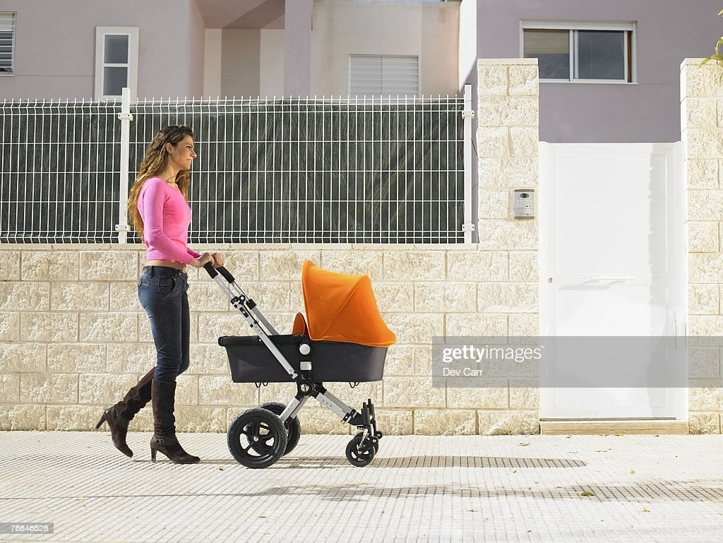 Mother pushing pram on pavement, Alicante, Spain, : Stock Photo