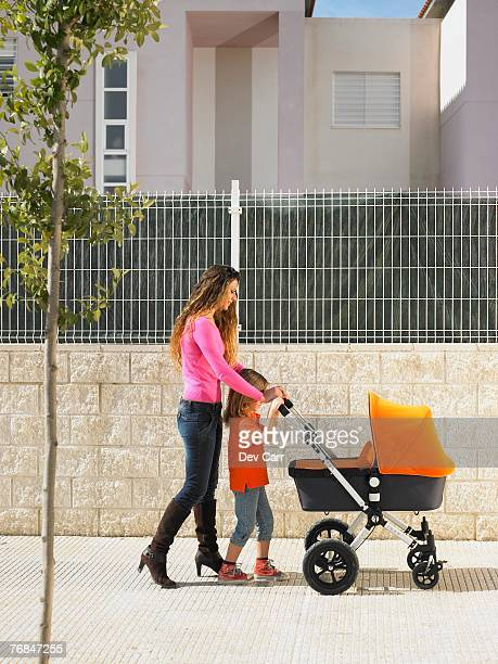 Mother pushing pram on pavement with young daughter (5-7), Alicante, Spain,