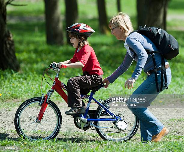 Mother pushing son on bicycle in park