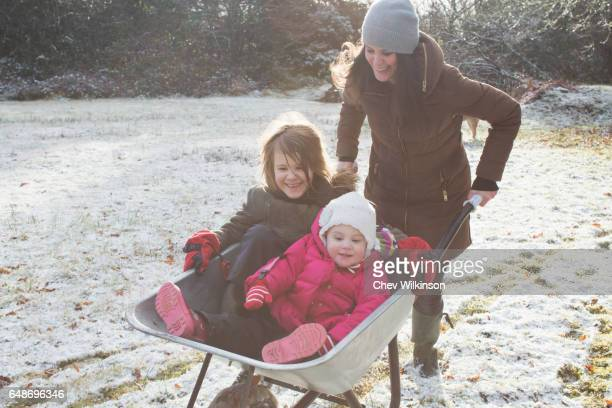 Mother pushing two daughters in a wheelbarrow, running