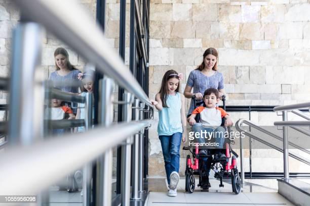 moeder duwen van de rolstoel met haar zoon op en zus lopen naast hem alle verlaten van de kliniek - handicap stockfoto's en -beelden