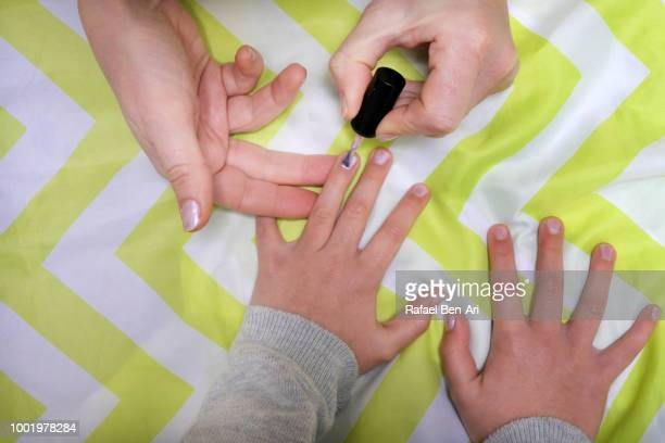 mother put on nail polish on her daughter fingers - rafael ben ari stock pictures, royalty-free photos & images