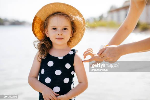 mother put sunblock cream on little daughter face at beach - uv protection stock pictures, royalty-free photos & images