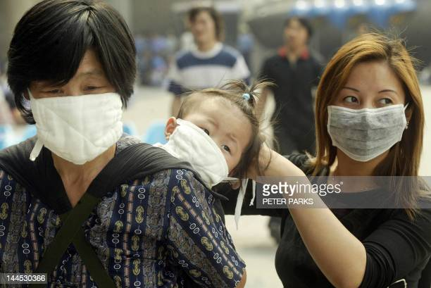 A mother puts a mask on her baby to protect against SARS in Beijing 02 June 2003 China reported no new cases of SARS for the first time since it...