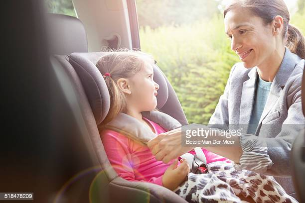 mother puts daughter in child car seat. - vehicle seat stock pictures, royalty-free photos & images