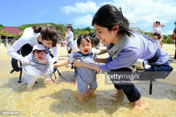 A mother puts her baby's legs into the sea during the Yoan Beach opening in Amami Oshima Island on April 18 2018 in Amami Kagoshima Japan This is...