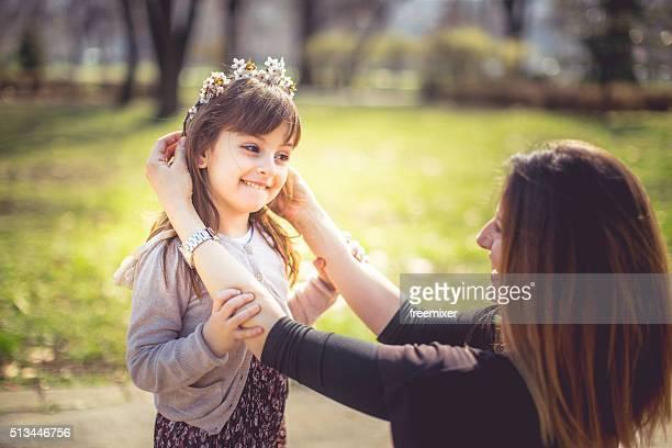 Mutter gibt Tochter im Frühling Kranz auf den har