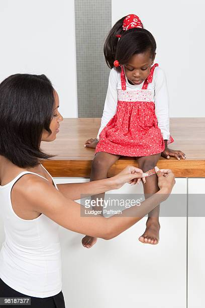 A mother putting a bandage on her daughter's knee