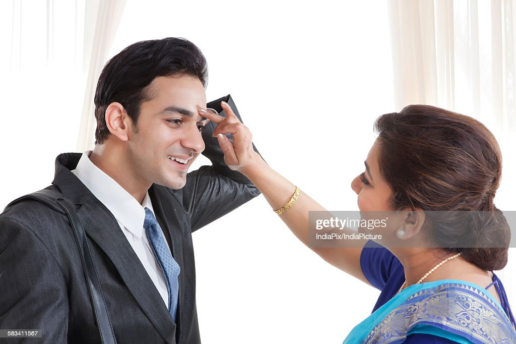 Mother putting a tikka on her sons forehead : Stock Photo