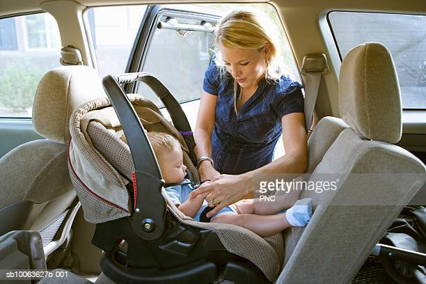 Mother putting baby boy (5 months) in car seat