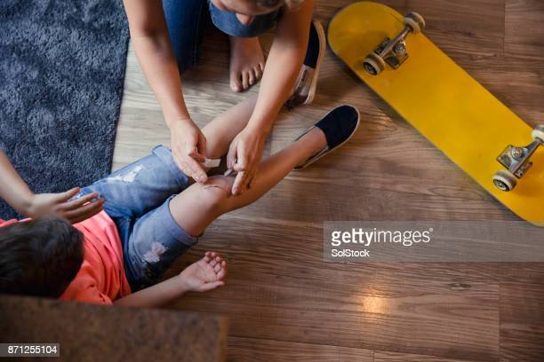mother putting band aid on childs knee. - machucado imagens e fotografias de stock