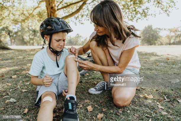 mother putting bandage on son's knee while sitting in public park during sunny day - verletzung stock-fotos und bilder