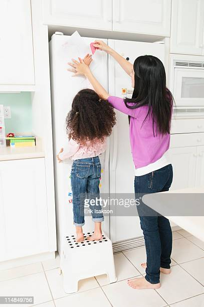mother putting daughter's drawing on refrigerator - artistic product stock pictures, royalty-free photos & images